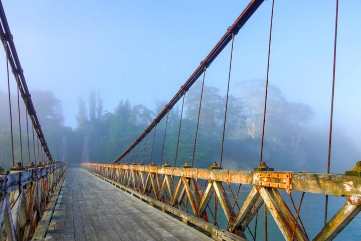Mystische Clifden Suspension Bridge im frühen Morgenlicht - nahe Tuatapere - Southern Scenic Route - Südinsel, Neuseeland